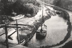 (04) Um 1900: Blick von der Galerie der Windmühle Spetzerfehn auf Klappbrücke, Kanal und die Werft Bokelmann (links).