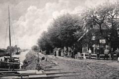 """(05) Johann Schoons Elternhaus um 1910. Am Giebel befindet sich ein Schild der Eisenbahn-Agentur, das Schild am Seiteneingang weist vermutlich auf die Poststelle hin.Es handelt sich um eine Ansichtskarte mit dem Vermerk auf der Rückseite: """"L. [= Loet] Schoon – Post- und Bahnagentur, Spetzerfehn""""."""