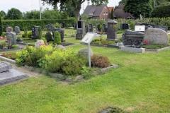"""(36) Auf dem Friedhof I in Spetzerfehn wurden 2017 auf Initiative des Ortsrats Informationstafeln zu den """"zwei Dichtern aus einem Haus"""" aufgestellt: Johann Schoon (1894–1968) und Greta Schoon (1909–1991). Auf dem Foto ist vorne das Grab Johann Schoons zu sehen, das Grab seiner Nichte Greta Schoon befindet sich rechts dahinter."""