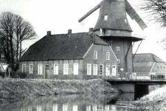 """(27) In den 1950er Jahren setzte überall ein großes Mühlensterben ein. Auch Spetzerfehn drohte seine Mühle zu verlieren, sie stand mehrere Jahre still. In dieser Zeit verfasste Johann Schoon das Gedicht <a href=""""https://johann-schoon.de/04-uns-olle-moehlen/"""">""""Uns olle Möhlen""""</a>. Dank glücklicher Umstände übernahm der Müllermeister Theodor Steenblock 1955 die Mühle Spetzerfehn, zunächst als Pächter, ab 1961 als Eigentümer. Sie ist nach wie vor in Familienbesitz und die einzige Mühle Ostfrieslands, die noch gewerbsmäßig mit Windkraft betrieben wird. Infos zur Geschichte der Windmühle Spetzerfehn (Mühle Steenblock) <a href=""""http://www.niedersaechsische-muehlenstrasse.de/index.php?id=475"""">hier</a>. Näheres über Windmühlen in Ostfriesland <a href=""""https://de.wikipedia.org/wiki/Liste_der_Windm%C3%BChlen_in_Ostfriesland"""">hier</a>. Auf dem Bild ist auch die neue Betonbrücke zu sehen, die die hölzerne Klappbrücke ersetzt hatte. Da die Schiffahrt auf den Fehnkanälen nach dem 2. Weltkrieg allmählich zum Erliegen kam, wurden die Klappbrücken nicht mehr gebraucht."""