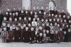 """(07) Spetzerfehn hatte ursprünglich drei Schulen. Die älteste war die """"Schule I"""" (Bild), die sich an der Bahnlinie in direkter Nachbarschaft von Johann Schoons Elternhaus befand. Hier gingen alle Kinder aus dem älteren (West-) Teil Spetzerfehns sowie dem angrenzenden Ulbargen zur Schule. Das Schulfoto von 1906 zeigt die Klassen 1 – 8. Der 12-jährige Johann Schoon ist in der oberen Reihe zu sehen (3.v.r.). Er war, wie später erzählt wurde, ein begabter Schüler, der von seinem Lehrer sehr gefördert wurde."""